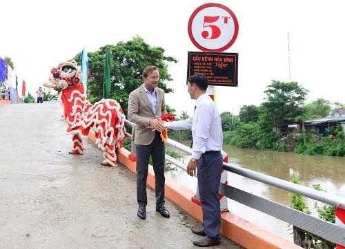 Ông Jacco van der Linden, Tổng giám đốc Điều hành Heineken Việt Nam (bên trái) cùng đại diện huyện Phú Tân kéo vải tấm biển khánh thành cầu Kênh Hòa Bình.