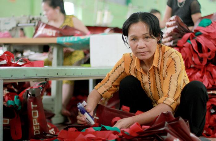 Chị Biên đang ghim tem mác cho túi chiều 8/10, mỗi ngày kiếm được vài chục nghìn đồng. Ảnh: Phan Dương.