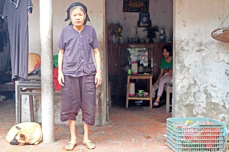 Bà Trần Thị Lung đangphải chăm sóc cho con trai nuôi tâm thần phân liệt, con dâuđầu óc không bình thường và 3 người cháu thiểu năng trí tuệ. Ảnh: Hải Hiền.