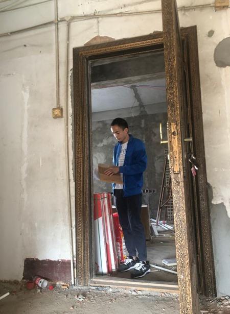 Anh Thích bên căn nhà 902 đang sửa sang dang dở, chưa biết khi nào mới có thể về ở. Ảnh: epaper.