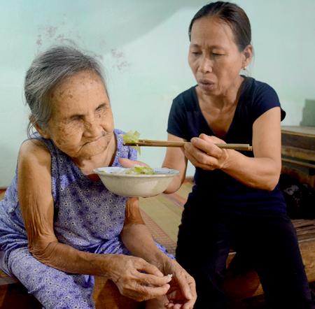 Bà Lê Thị Mộng Thu đút canh cho cụ Mịch ăn. Ảnh: Đắc Thành.