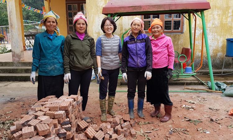 Chị Lee cùng người dân địa phương xây nhà nên sưởi mẫu tại huyện Văn Hồ, tỉnh Sơn La tháng 11/2019. Ảnh: K.Y.L.