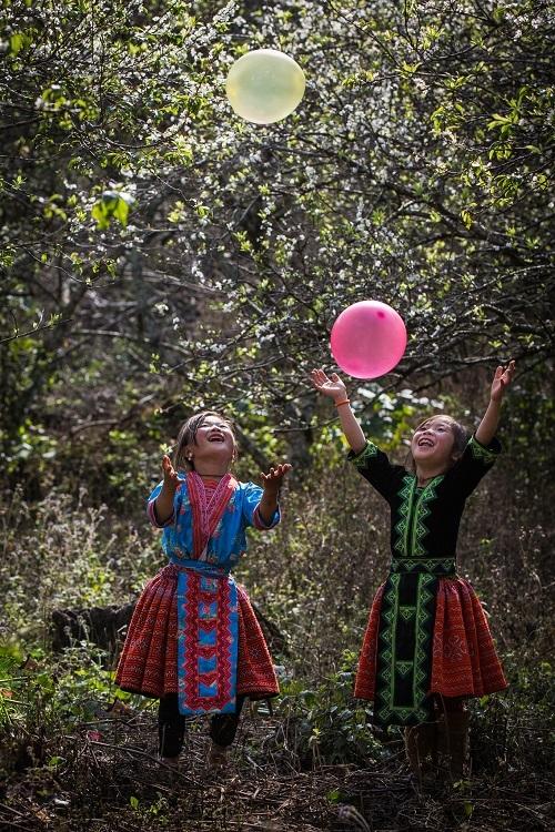 Trong các tác phẩm của Trần Tuấn Việt, có nhiều bức ảnh về trẻ em. Anh chia sẻ, muốn lưu giữ những khoảnh khắc bình yên, giản dịở những làng quê vì đó là nơi gợi lại những kýứcđẹpđẽ của tuổi thơ.Trong bức ảnh trên, hai em bé người HMongở Mộc Châu đang chơiđùa cùng bóng bay.