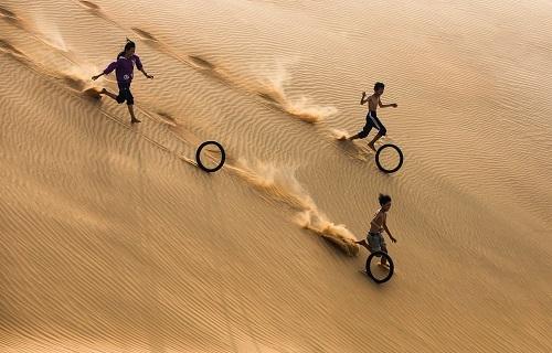 Một nhóm trẻ em chơi đùa với lốp xe cũ trênđồi cát bay ở Mũi Né, Phan Thiết. Niềm vui từ trò chơi đơn giản này khác xa với những trò chơi điện tử đắt đỏ của trẻ em thành phố. Đây là trò chơi thú vị của trẻ em khắp thế giới, nhiếp ảnh gia kể.