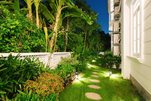 Hàng rào giữa đường chính và ngôi nhà bao quanh bởi cây xanh, những nan gỗ thấp xinh xắn sơn trắng tạo cảm giác gần gũi với chủ nhân, khách mỗi khi ghé thăm.