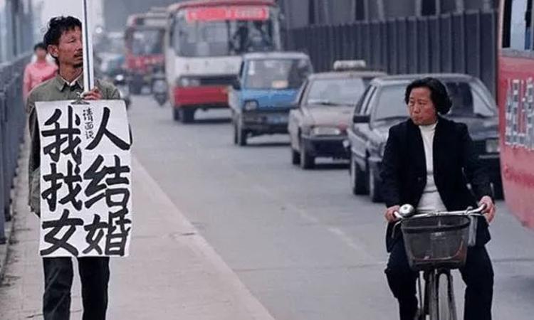 Một người đàn ông cầm biển đề: Tôi muốn tìm một phụ nữ để kết hôn trên đường phố tại tỉnh Quảng Đông. Ảnh: sohu.