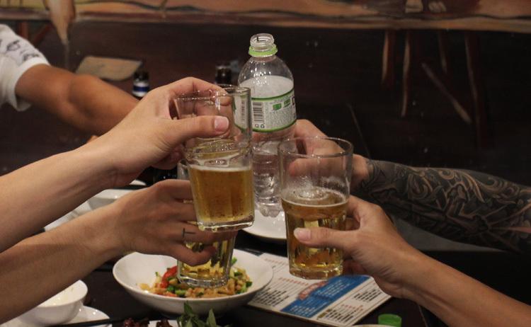 Hội nhậu 5 người, 4 người đi xe ôm uống bia, người còn lại tự đi xe máy nên chọn uống nước lọc. Ảnh: Phan Diệp.