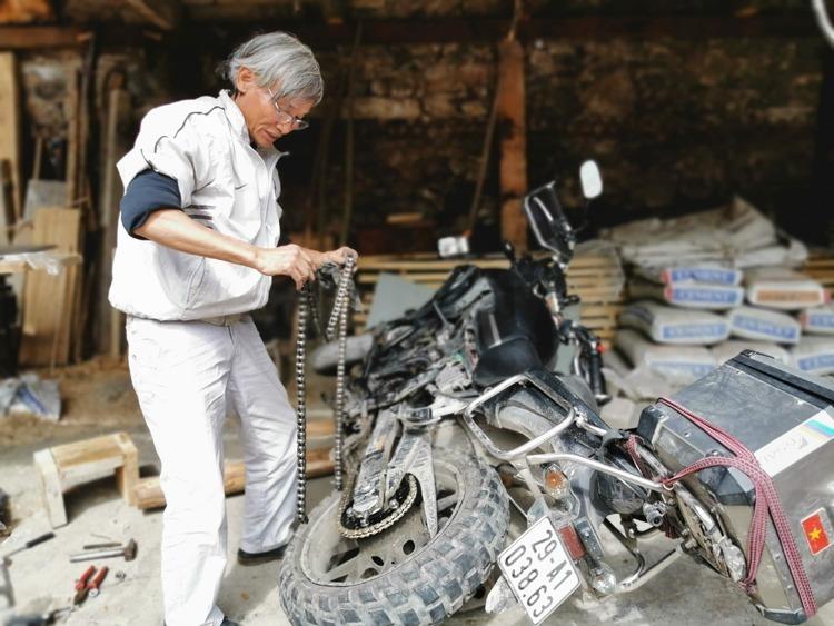 Ông Hùng tự tay sửa xe trên đường đi. Ảnh: NVCC.