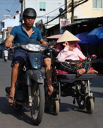 Anh Trí đi xe máy đẩy chiếc xe lăn của vợ về phòng trọ. Ảnh: Phan Diệp.