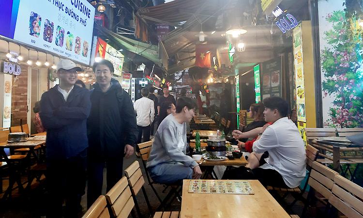 Các quán nhậu bày sẵn bàn ghế, lấn chiếm vỉa hè đón khách tại phố Tạ Hiện, quận Hoàn Kiếm, Hà Nội,trong chiều tối ngày 13/1. Ảnh: Phạm Nga.