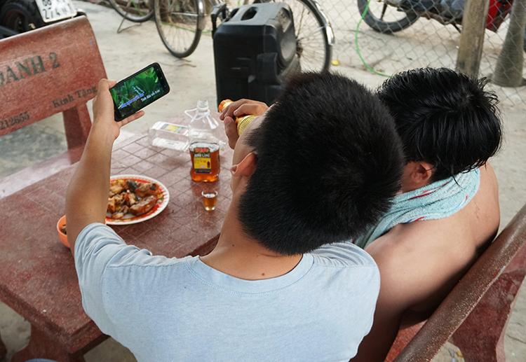 Chai rượu, đĩa mồi và màn karaoke bằng loa kéo là thói quen của nhiều người. Ảnh chụp tại một xóm trọ tại quận 9, TP HCM lúc 17h ngày 18/1. Ảnh: Phan Diệp.