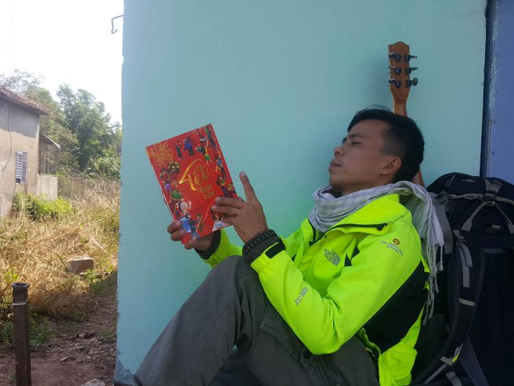 Hồ Nhật Hà trongngôi nhà bỏ không tình cờ gặp ở Bình Phước, với hành trang là sách, đàn ghi ta, bên cạnh một ba lô các thứ thiết yếu. Ảnh: Nhân vật cung cấp.