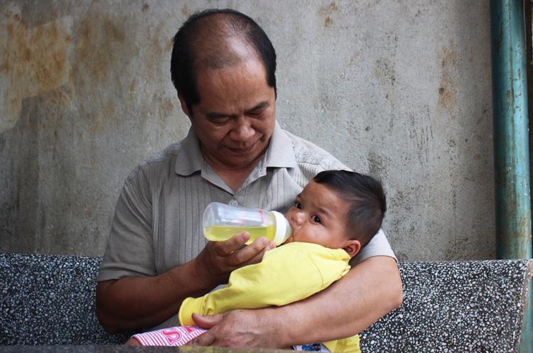 Ông Nhật và bé Đinh Thiên Đức, 11 tháng tuổi. Vừa lọt lòng, bé Đức đã bị bỏ rơitrên rẫy và được ông Nhật mang về nuôi. Bé bị phát hiệnbệnh tim bẩm sinh từ khi 2 tháng tuổi, cha nuôi đã phải bán bò để đưa bé đi mổ. Sau hai lần phẫu thuật, đến nay bé Đức đã ổn. Ảnh: Phan Diệp.