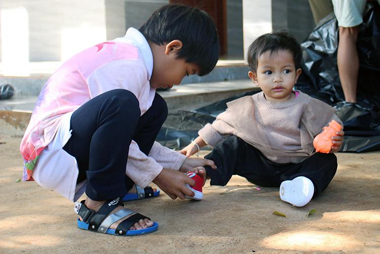 Bé Rahlan H Ưn dân tộc Gia Rai. 6 tuổi (bên trái), được ông Nhậtnhận nuôi lúc 1 tuổi,do cha mẹ mất sớm và béĐinh Thị Thùy Trâm (bên phải), 1 tuổi. Bé Trâm được nhận về từlúc 4 tháng. Mẹ bémất sớm, bà ngoại già không nuôi nổi nên đem đến gửi ông Nhật. Ảnh: Phan Diệp.