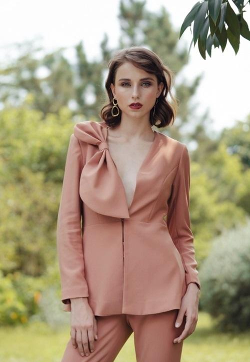 Áo vest tuytsi HeraDG - WT19019A thu hút nhiều chị em nhờ kiểu dáng thời trang, màu nâu trung tính sành điệu. Thiết kế có phần cổ xẻ ngực sâu, thắt nơ bản to ở ngực phải, giấu khuy và lụa bóng thoát mát. Sản phẩm có giá 1,398 triệu đồng.