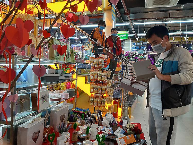 Tối 13/2, nhiều người đeo khẩu trang y tế đến chọn quà cho người yêu tại một cửa hàng quà tặng trên phố Xuân Thủy, phố Cầu Giấy, Hà Nội. Ảnh: Nhật Minh.