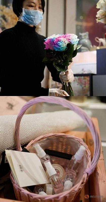 Cai Xiaoman tặng nước khử trùng cho khách mua hoa. Ảnh: Reuters.