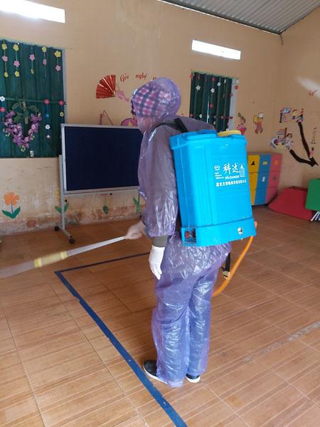 Cô giáo ở điểm trường xã Sủng Là, Đồng Văn, Hà Giang mặc áo mưa, đeo khẩu trang khử trùng lớp học. Ảnh: Phạm Phương Hồng.