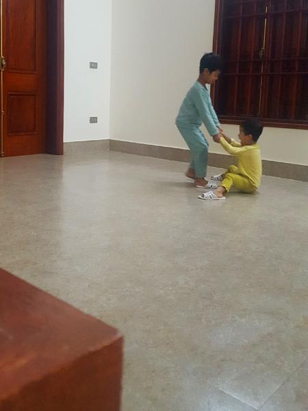 Sàn trơn trượt, hai con của chị Hoa thích thú kéo nhau trượt patin khắp nhà. Ảnh: Mai Nhị.