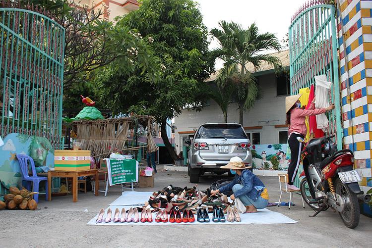 Cô giáo mầm non Bích Phương đang bày những đôi giày để chuẩn bị cho buổi bán hàng tối 21/2. Ảnh: Phan Diệp.