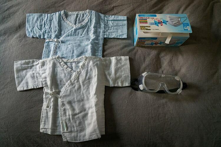 Vigor Liu chuẩn bị sẵn quần áo, khẩu trang và kính bảo hộ cho đứa con sắp chào đời. Ảnh:  Giulia Marchi/The New York Times.