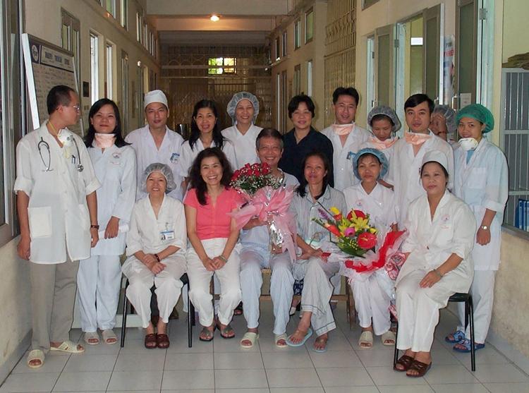 Y tá Nguyễn Thị Thục (người đầu tiên bên phải) cùng các đồng nghiệp chụp hình lưu niệm với bệnh nhân Sars, ôngHùng (ôm hoa hồng). Ảnh: Nhân vật cung cấp.