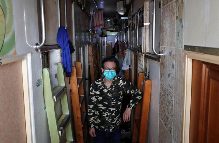 Simon Wong đứng trước căn hộ quan tài rộng 2 m2 của mình. Ảnh: Reuters.