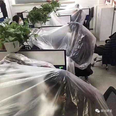 Nhân viên văn phòng tại tỉnh Hồ Bắc chùm kín áo mưa phòng bệnh Covid 19 khi làm việc. Ảnh: sohu.