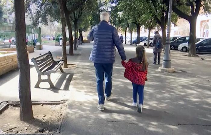 Một bé gái đi dạo cùng ông dọc theo một hàng cây ở Rome, Italy, hôm 5/3 sau khi chính phủ đóng cửa tất cả các trường học để hỗ trợ cuộc chiến chống Covid-19. Ảnh: AP