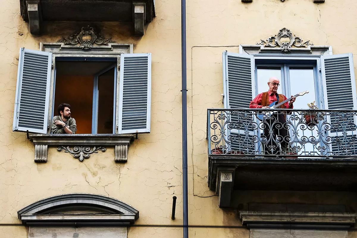 Một người đàn ông đang chơi đàn ngoài ban công ở Turin. Kể từ khi toàn quốc bị phong tỏa, người dân Italy thường giải tỏa bằng cách ra ban công chơi đàn hoặc hát động viên nhau. Ảnh: Vox.