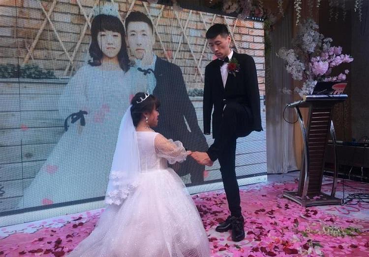 Chú rể trao nhẫn cho vợ bằng chân trái trong hôn lễ. Ảnh: Kuaibao.