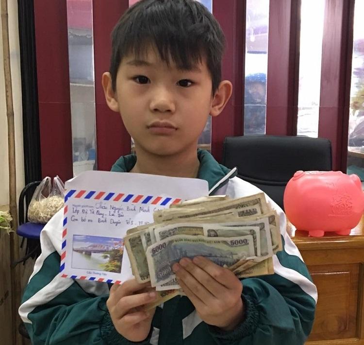Bé Minh mang heo nhựa đến hội thiện nguyện mổ để ủng hộ tiền phòng Covid-19. Ảnh: Hưng Huế.