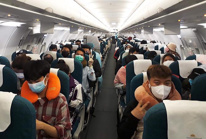 Lưu học sinh trên chuyến bay của Vietnam Airlines về nước. Ảnh: VNA.