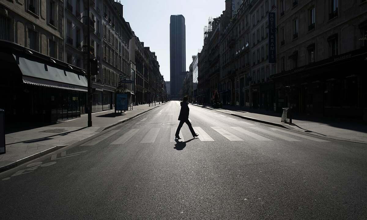 Một phụ nữ băng qua con đường vắng vẻ ở Paris trong thời kỳ phong tỏa. Ảnh:Thibault Camus/AP.