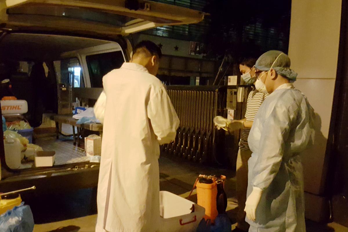 Bác sĩ Hồng (quần áo bảo hộ), kỹ thuật viên Hải Linh áo blouse tác nghiệp tại chung cư Tràng An, đêm 7/3. Ảnh: Danh Nhẫn.