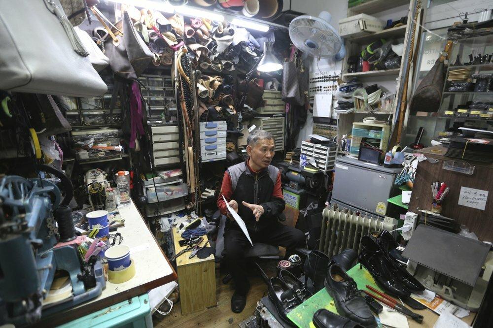 ÔngKim Byung-rok trong cửa hàng sửa chữa giày của mình ở Seoul, Hàn Quốc. Ảnh: AP.