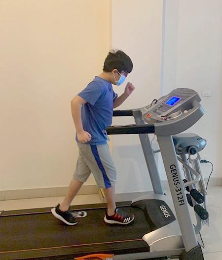 Con trai thứ hai của chị Linh thường xuyên tập thể dục bằng máy chạy bộ trong nhà thay vì ra ngoài đá bóng như trước đây. Ảnh: Vương Linh.