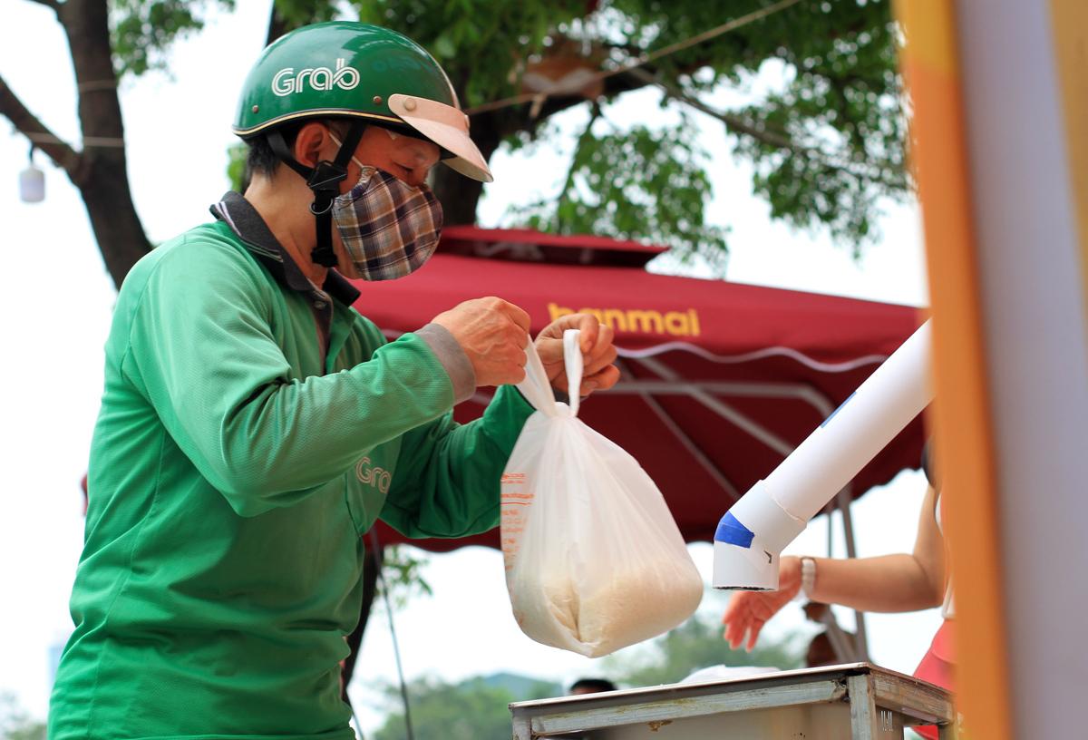 Lực lượng xe ôm bị ảnh hưởng bởi dịch. Những túi gạo miễn phí giúp họ chắc bụng hơn ở thời điểm này. Ảnh: Phan Dương.