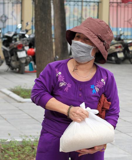 Bên cạnh cây ATM nhả gạo tự động, điểm phát gạo miễn phí cũng chuẩn bị sẵn những túi gạo đưa cho người già, người khuyết tật, người có con nhỏ để họ không phải xếp hàng. Trong ảnh, bà Tuyết cảm ơn khi được tặng gạo. Ảnh: Phan Dương.