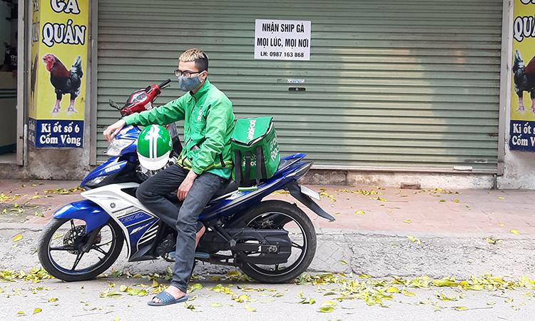 Một shipper đứng đợi nhận hàng tại một quán ăn trên đường Cốm Vòng, quận Cầu Giấy, Hà Nội. Ảnh: Phạm Nga.