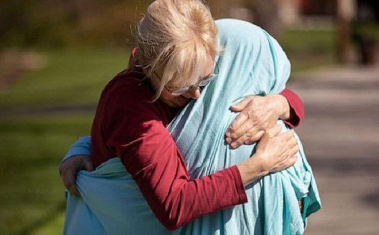 Bà Cheryl ôm lấy con gái là y tá sau một tháng xa nhau bằng cách trùm chăn lên người con. Ảnh:Liz Dufour.
