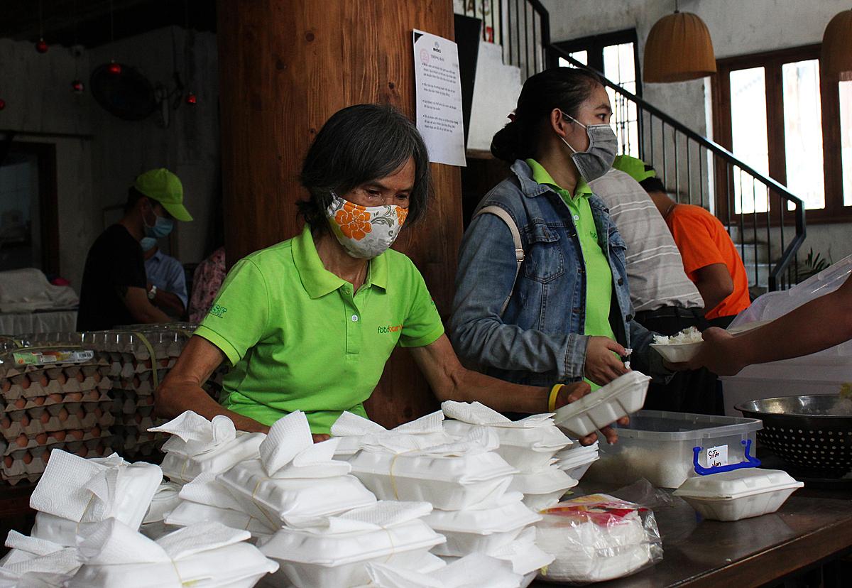 Bà Nghiêm Vân Hồng (70 tuổi), là một tình nguyện viên của quán cơm dã chiến. Có mặt từ 7h, bà phụ nấu trong bếp, sau đó phụ việc cho cơm vào hộp. Ảnh: Diệp Phan.