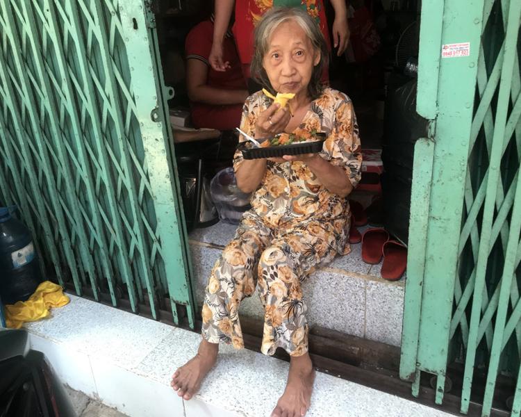 Bà Láng ngồi trước cửa nhà thưởng thức cơm từ thiện. Ảnh: K.A
