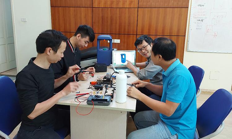 Anh Nguyễn Hữu Phước Nguyên (người đeo kính) cùng anh Hàn Huy Dũng và nhóm kỹ sư nghiên cứu dự án máy rửa tay không chạm. Ảnh: Nhân vật cung cấp.