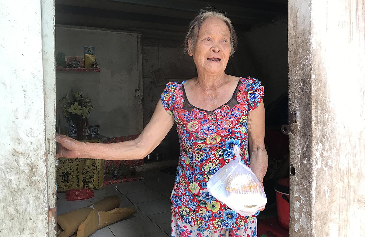 Bà Châu, mẹ anh Minh xúc động khi nhận được cơm từ thiện của chương trình Tiếp sức cộng đồng - Vững vàng vượt khó do Grab và Quỹ Hy Vọng tổ chức. Ảnh: Kim Anh.