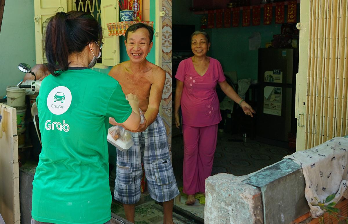 Người nghèo ở quận 11 vui mừng khi nhận cơm từ thiện từ chương trình Tiếp sức cộng đồng - Vững vàng vượt khó do Grab và Quỹ Hy vong tài trợ.