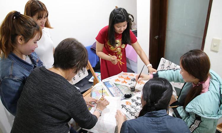Chị Xuân Trang hướng dẫn viết tiếng Trung bằng bút lông cho các lao động Việt tại Đài Bắc trong một buổi học. Ảnh: Nhân vật cung cấp.