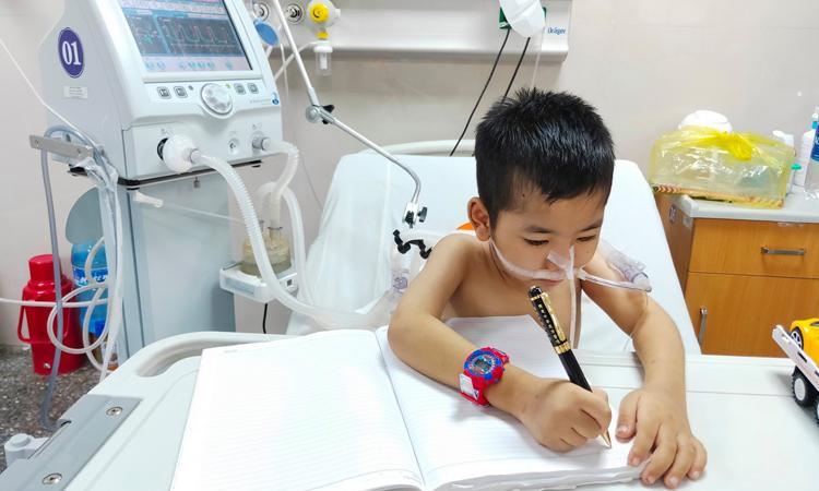 Nguyễn Minh Đức những ngày đầu ngồi dậy tập viết ngay trên giường bệnh. Ảnh: Ngọc Hân.