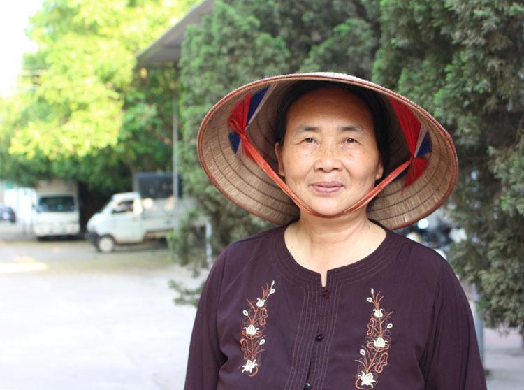 Trang phục thường thấy của bà giám đốc doanh nghiệp là nón lá, bộ áo nâu sòng và dép tổ ong hoặc chân đất. Ảnh: Phạm Nga.