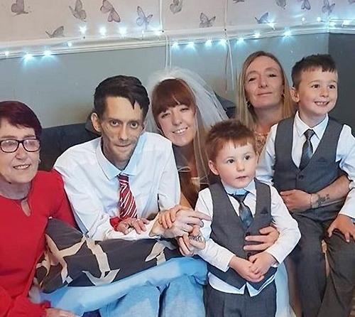 Vợ chồng Kristy cùng hai con trai và người thân trong hôn lễ được tổ chức tại phòng khách. Ảnh: MEN Media.
